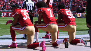 Eric Reid #35, Colin Kaepernick #7 and Eli Harold #58 of the San Francisco 49ers kneel in protest during the national anthem prior to their NFL game against the Tampa Bay Buccaneers at Levi's Stadium on October 23, 2016 in Santa Clara, California.