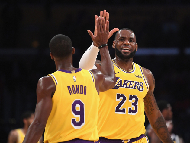 LeBron James #23 of the Los Angeles Lakers high fives Rajon Rondo #9 during a preseason game against the Denver Nuggets at Staples Center on October 2, 2018 in Los Angeles, California.