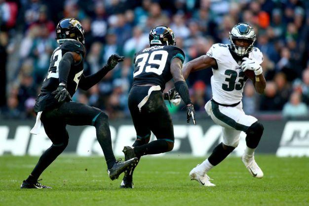 Josh Adams #33 of Philadelphia Eagles avoids a tackle from Tashaun Gipson Sr. #39 and Quenton Meeks #43 of Jacksonville Jaguars during the NFL International Series game between Philadelphia Eagles and Jacksonville Jaguars at Wembley Stadium on October 28, 2018 in London, England.