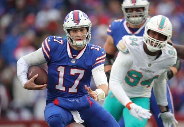 Josh Allen #17 of the Buffalo Bills runs with the ball in the second quarter during NFL game action as he is chased by Robert Quinn #94 of the Miami Dolphins at New Era Field on December 30, 2018 in Buffalo, New York.